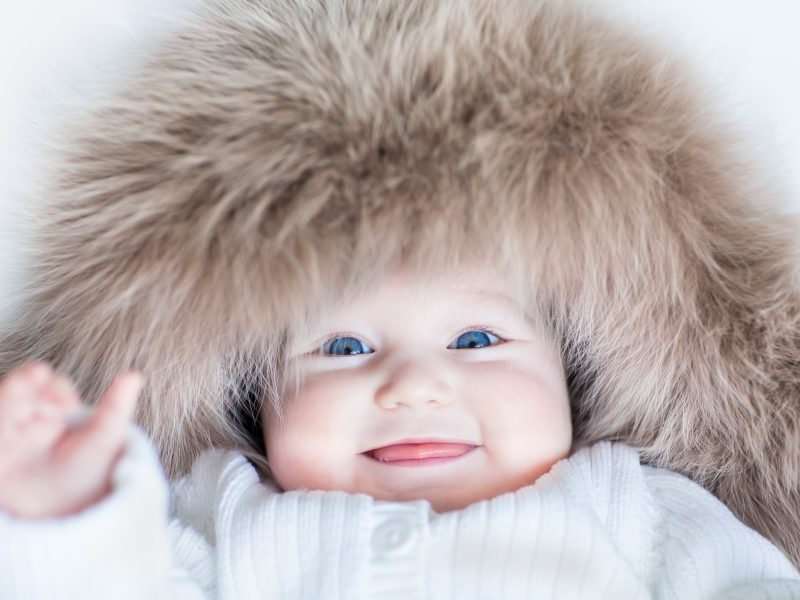 Funny cute baby girl with big blue eyes wearing a huge winter ha